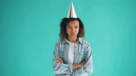 bad mood : Portrait of unhappy mixed race girl in party hat standing with arms crossed and looking at camera with sad face. Bad mood, birthday and negativity concept.