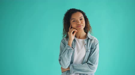 denken : Portrait of pretty African American woman in trendy outfit thinking dreaming on blue background looking at camera and smiling. People and thoughts concept. Stockvideo