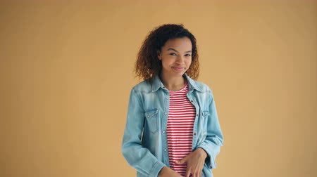 coqueteo : Portrait of beautiful African American woman looking at camera flirting smiling touching pretty curly hair wearing trendy clothing. Youth and dating concept. Archivo de Video
