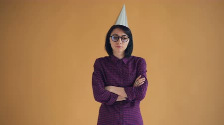 cheerless : Portrait of unhappy brunette in bright party hat standing with crossed arms and looking at camera with sad face. Bad mood, birthday and sadness concept. Stock Footage