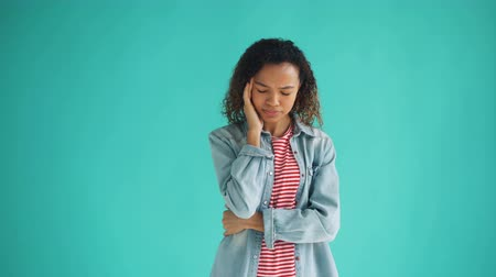 мрачный : Portrait of sick African American woman suffering from headache touching head feeling bad standing on blue background. Unhealthy people and migraine concept.
