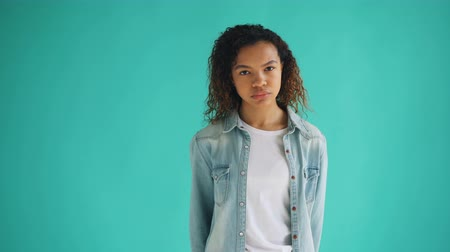 мрачный : Portrait of sad African American girl in trendy denim shirt standing alone with unhappy face looking at camera. Millennials, ethnicity and sadness concept. Стоковые видеозаписи