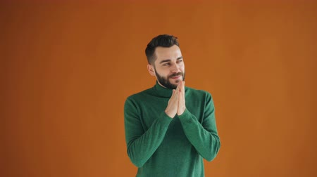 villain : Portrait of cunning guy rubbing his hands and smiling looking at camera with sly face standing on orange background. People and bad intentions concept.