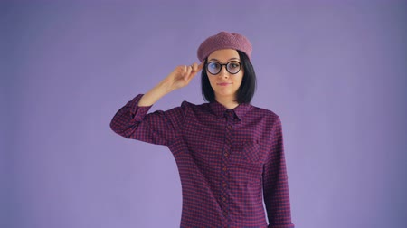 significado : Portrait of female hipster twisting finger at head making fool sign looking at camera shrugging shoulders standing alone on violet background. People and attitude concept.