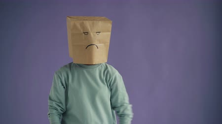 disfarçar : Portrait of displeased person with paper bag on head showing thumbs-down gesture expressing dislike and negativity standing against purple background.