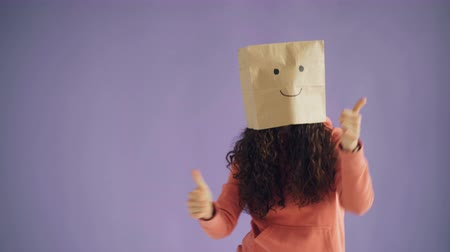 jóváhagyás : Portrait of slender girl with paper bag on head dancing showing thumbs-up showing like sign moving on purple background. People and appreciation concept. Stock mozgókép