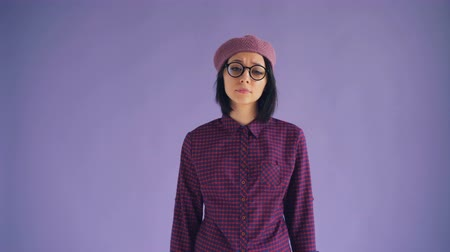 bailler : Portrait of sleepy brunette in glasses and hat yawning looking at camera feeling tired standing against purple background with bored face. Millennials and human emotions concept. Vidéos Libres De Droits