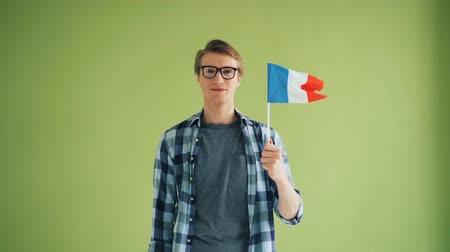 nationality : Slow motion portrait of good-looking guy with French flag looking at camera and smiling while standing on green background. Youth and patriotism concept.