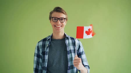 kanada : Slow motion portrait of male partiot holding Canadian flag and smiling looking at camera against green background. Happy youth, patriotism and countries concept. Stok Video