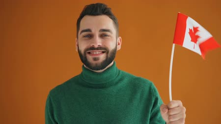 canadian maple leaf : Slow motion portrait of bearded young student with Canadian flag smiling looking at camera on orange background. Youth, countries and patriots concept.
