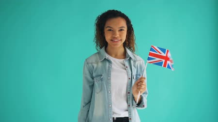 гордый : Slow motion portrait of cute African American lady with British national flag smiling looking at camera on blue background. Great Britain and people concept. Стоковые видеозаписи