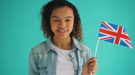 büszke : Slow motion of pretty mixed race woman with curly hair holding flag of England smiling on blue background. African American people, youth and patriotism concept.