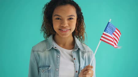 гражданство : Slow motion portrait of attractive mixed race girl holding national American flag and smiling standing on blue background. World counties and symbols concept.