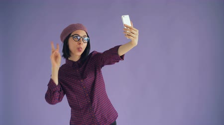 photograph : Portrait of playful young woman taking selfie with smartphone camera showing hand gestures and tongue posing enjoying activity on light purple background.