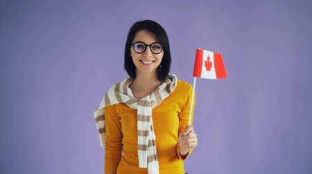 kanada : Slow motion of female Canadian hipster holding national flag smiling looking at camera standing alone feeling happy. Patriotic youth and countries concept. Stok Video