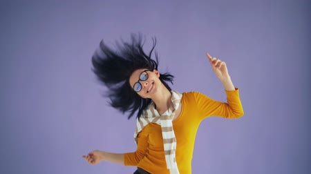 camera move : Slow motion of pretty female hipster jumping moving head waving black hair having fun on purple background. Joyful young people and freedom concept.