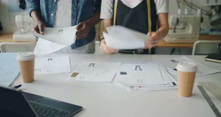 couturier : Creative people are working in fashion designing studio holding sketches looking for ideas pointing at drawings. Creative work, dressmaking and workplace concept. Stock Footage