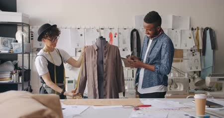varrónő : Female tailor is measuring garment while African American man her colleague is writing in notebook talking smiling. Fashion design and handmade clothes concept.