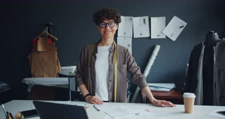 varrónő : Portrait of smiling young lady self-employed seamstress looking at camera standing in studio alone. Successful millennials, start-up and small business concept.