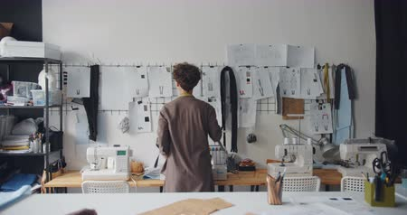 couturier : Tailor young lady touching drawings on wall planning new clothes collection standing with her back to camera. Fashion design and creative people concept. Stock Footage