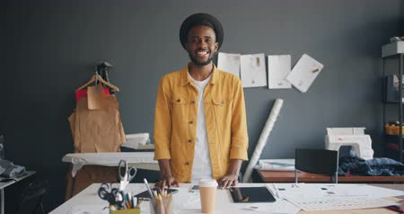 couturier : Portrait of handsome African American designer smiling standing at work looking at camera enjoying small business. Fashion design, job and millennials concept.