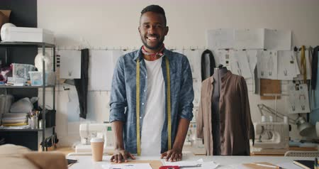 couturier : Portrait of male clothes designer looking at camera smiling standing in studio with tailors dummy. Fashion design, profession and small business concept.