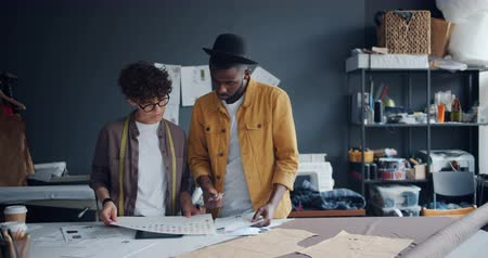 couturier : Clothes designers Caucasian girl and African American guy choosing color for new garment looking at papers working in studeio together. Design and style concept.