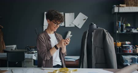 saçlı : Female fashion designer pretty curly-haired young woman in glasses is using smartphone during break at work smiling touching screen enjoying modern technology.
