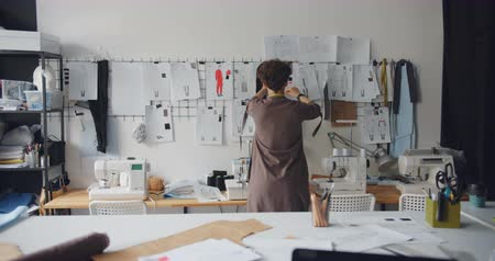couturier : Female clothes designer slender brunette is looking at drawings of garments hanging on wall touching sketches working in studio alone. People and profession concept.