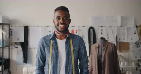 портной : Portrait of creative young tailor African American man smiling in studio looking at camera expressing positive emotions. Successful start-up and youth concept.