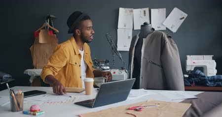 couturier : Trendy tailor African American man is measuring garment on dummy then writing in notebook working alone in workshop. Creative people, workplace and job concept.