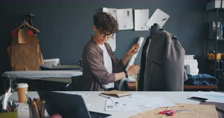 couturier : Pretty seamstress is measuring garment on tailors dummy then writing information in notebook creating stylish handmade clothes. Profession and workplace concept.