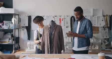 varrónő : African American man and Caucasian girl tailors are measuring clothes on dummy writing measurements in notebook working in modern studio. People and work concept.