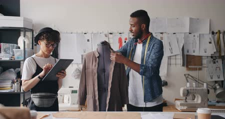 couturier : Tailor African American man is measuring clothes on mannequin while Caucasian girl colleague working with tablet assisting. Fashio design and people concept. Stock Footage