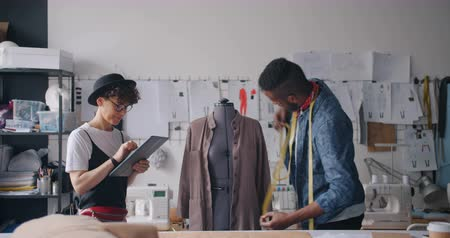 terzi : People designers African American guy and Caucasian lady are measuring clothing on tailors dummy and using tablet to put in measurements. Technology and fashion concept. Stok Video
