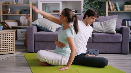 lét : Flexible husband and wife are exercising at home together doing yoga for couples on floor stretching body and smiling. Health and relationship concept.