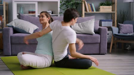 jimnastik : Happy young couple Caucasian woman and Asian man are doing yoga together bending body backwards in pairwork enjoying exercise. Youth and activity concept. Stok Video