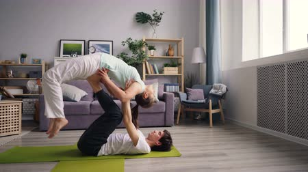 together trust : Cute couple young flexible students are practising yoga position exercising together at home. Guy is lying on floor on mat and supporting girl balancing in air.