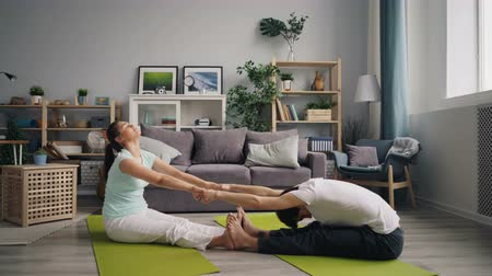 hatha : Man and woman young married people are doing stretching exercises holding hands sitting on mats at home relaxing. Active lifestyle and healthcare concept.