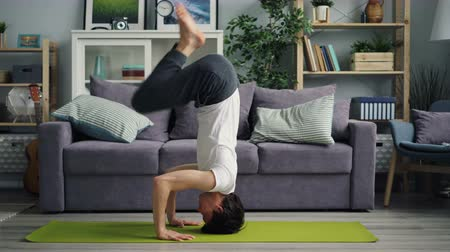 flat head : Handsome Asian guy is doing headstand during yoga practice at home alone standing on arms and head on bright mat. Healthy sportive people and house concept.