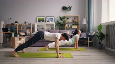 emelkedő : Girl and guy healthy young people are doing yoga asanas in nice apartment training on mats together practising downward and upward dog position. Stretching and house concept.