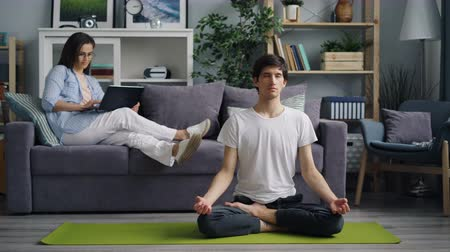 mindennapi : Young man husband is meditating on yoga mat while woman is working with laptop smiling enjoying modern technology. Happy family and leisure time concept.