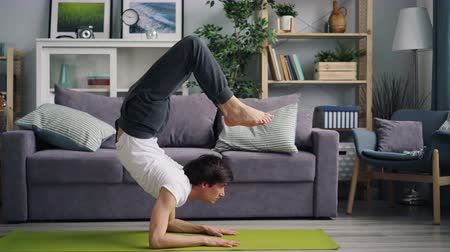 flat head : Attractive Asian guy doing yoga asanas handstand and headstand at home then moving into crab position and relaxing on mat. Healthy people and practice concept.