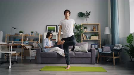 daily : Handsome Asian man is doing yoga practice while girlfriend is working with laptop sitting on sofa at home. Family, hobby and modern lifestyle concept. Stock Footage