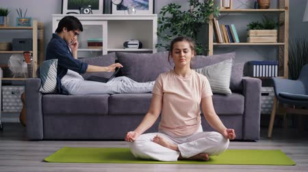 mindennapi : Young lady housewife is meditating in lotus position while guy is talking on mobile phone using laptop working at home. People, modern technology and meditation concept.
