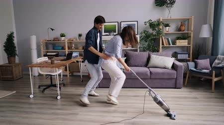 domácí práce : Husband and wife playful young people are vacuuming floor dancing having fun in modern apartment listening to music. Youth, joy and household concept.