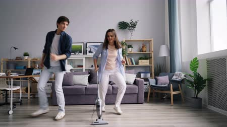 em casa : Young family husband and wife are dancing singing during housework using vacuum cleaner at home enjoying housekeeping and entertainment. Youth lifestyle concept.