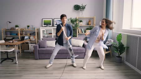 コミカル : Playful couple man and woman are having fun with vacuum cleaner dancing laughing enjoying leisure time in modern apartment. Family, love and joy concept.