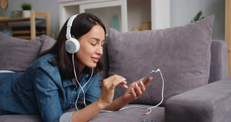 enjoyable : Happy student attractive girl is listening to music in headphones holding smartphone touching screen lying on sofa at home. Gadgets, youth and leisure concept. Stock Footage