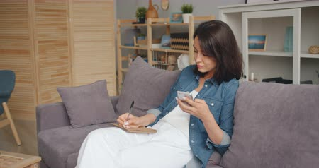 メッセンジャー : Young lady is taking notes in notebook looking at smartphone screen sitting on couch in house using modern gadget. Millennials and technology concept. 動画素材